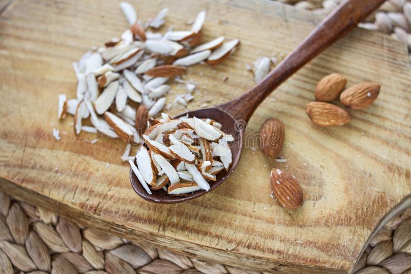 Un manojo de nueces enteras y tajadas de la almendra en un tablero de madera y en una cuchara de madera del roble en la tabla foto de archivo
