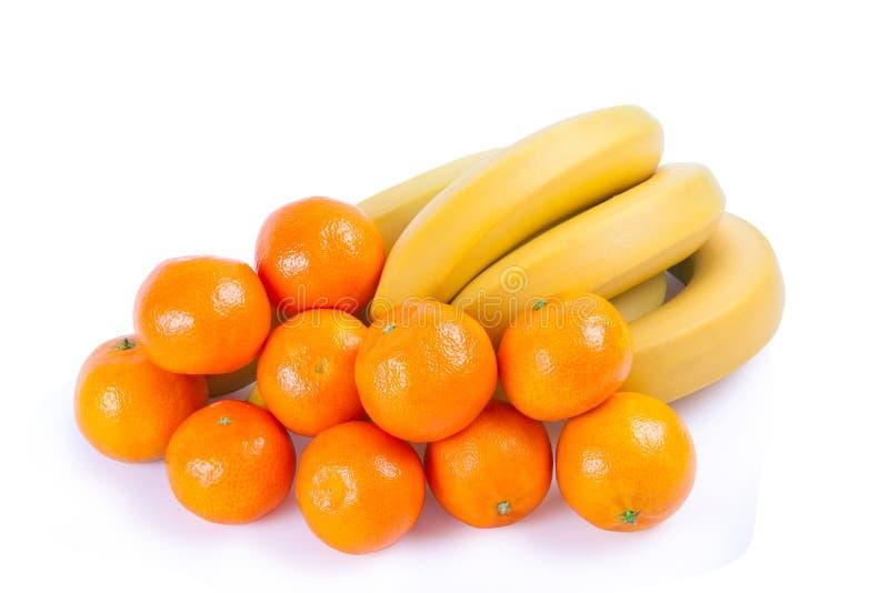 Un manojo de plátanos y de mandarines foto de archivo