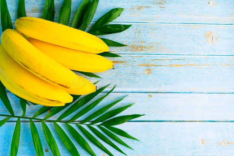Un manojo de plátanos y de hojas de palma en un fondo de madera Copie el espacio imagen de archivo libre de regalías