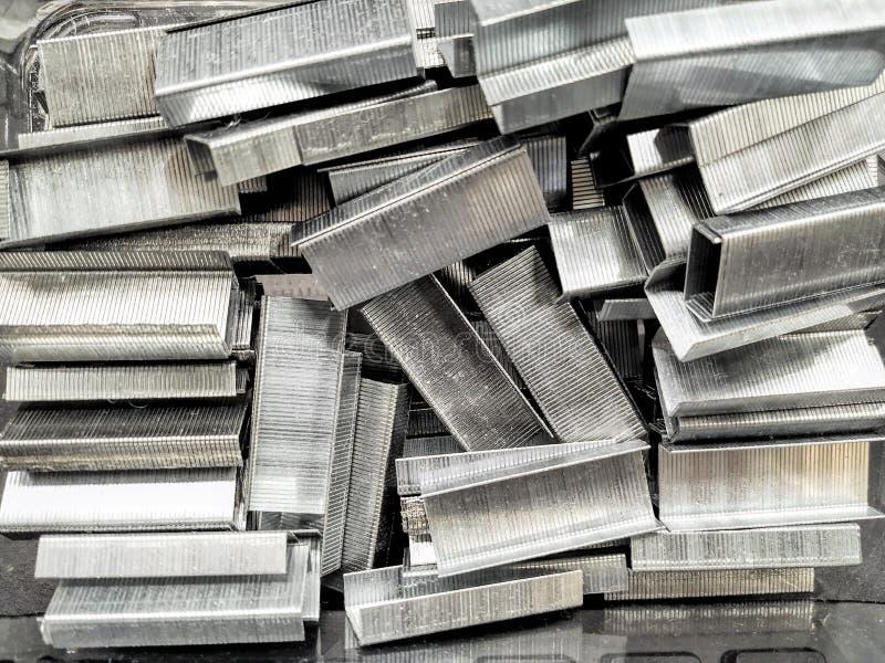 Un manojo de soportes para una grapadora para las hojas que sujetan con grapa, trabajo de oficina imagenes de archivo