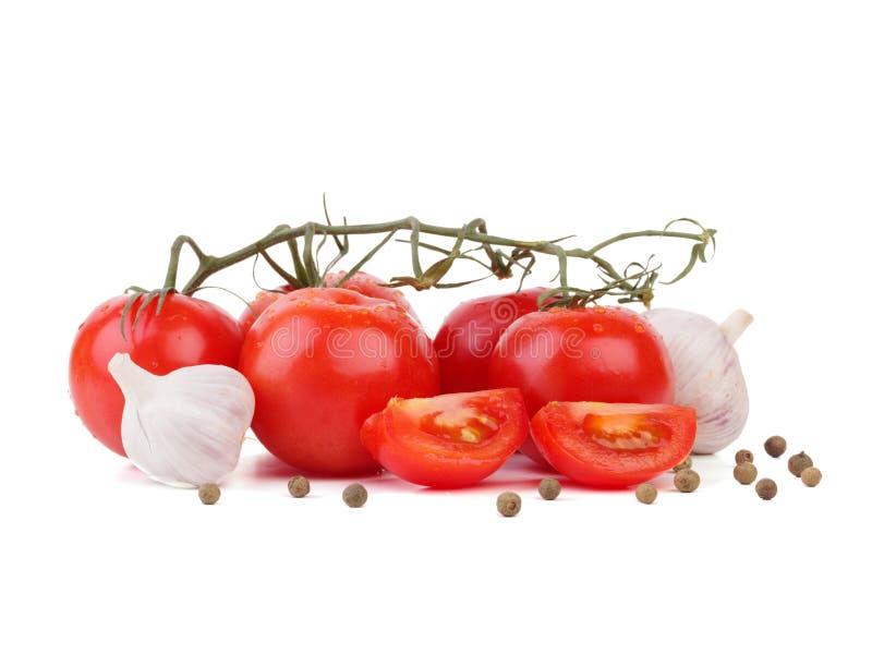 Un manojo de tomates del jardín con ajo imagenes de archivo