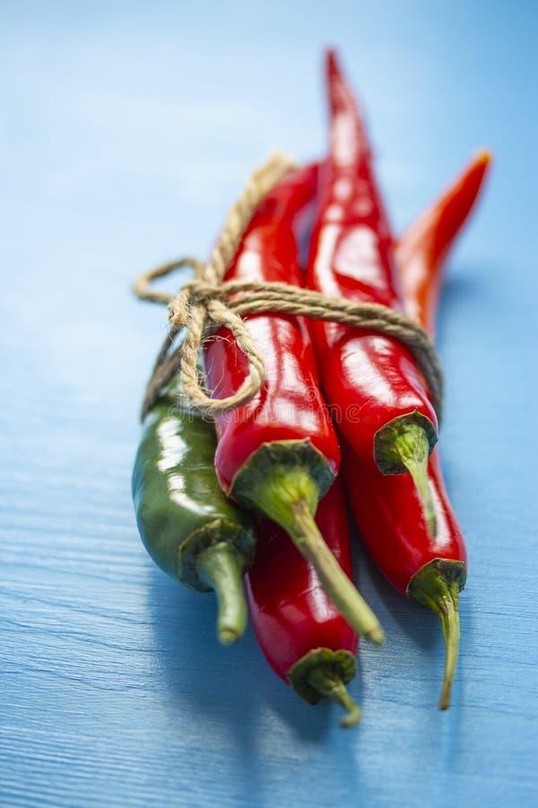 Un manojo de verde rojo de las pimientas de chile atado con guita en un fondo de madera azul Chile del jalapeno del pimiento pica imagenes de archivo