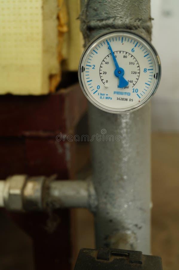 Un manometro dell'acqua sul condotto termico fotografia stock