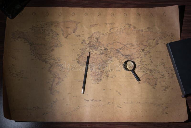 Un mapa de Viejo Mundo, una lupa, un lápiz y una libreta fotos de archivo