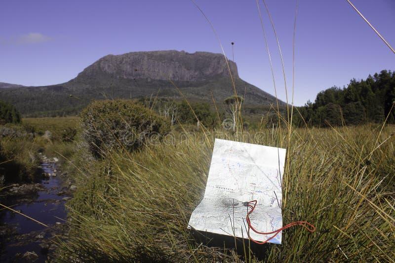 Un mapa y un compás en un llano de los buttongrass delante de una escarpa rocosa en la pista terrestre de Tasmania Australia fotografía de archivo