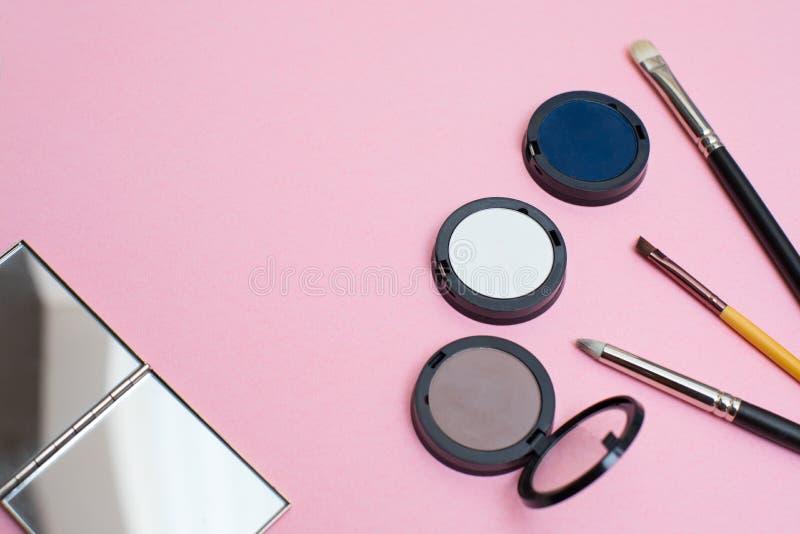 Un maquillaje fijado en un fondo rosado: cepillos del maquillaje, sombreadores de ojos, y un espejo Composición creativa de la en fotografía de archivo libre de regalías