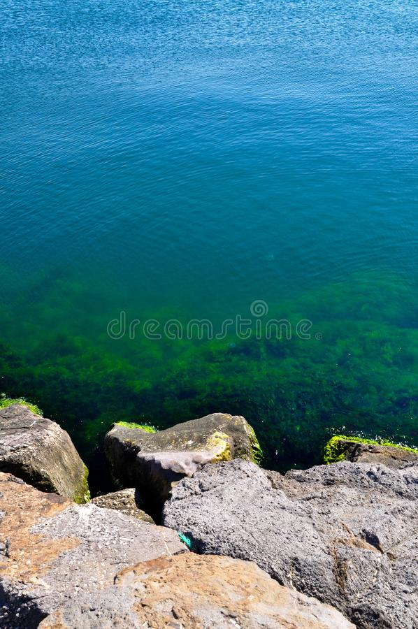 Un mar azul tranquilo y rocas imagenes de archivo