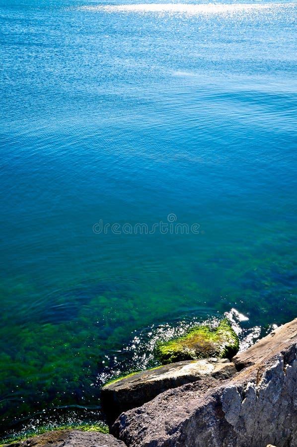 Un mar azul tranquilo y rocas foto de archivo libre de regalías