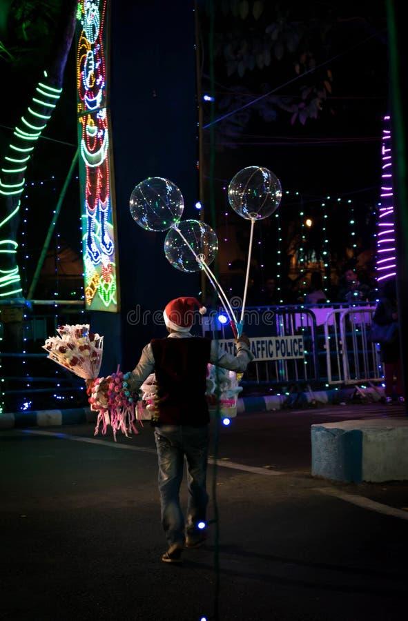 Un marchand ambulant vend son produit la nuit de festival dans Kolkata photo stock
