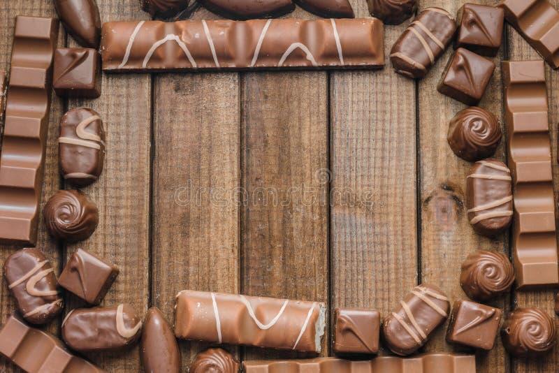 Un marco de los caramelos y de las barras de chocolate en un fondo de madera fotos de archivo