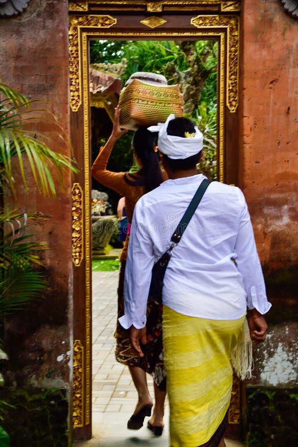 Un marito e una moglie di balinese che indossano abbigliamento locale tradizionale che entra in un tempio sacro immagine stock