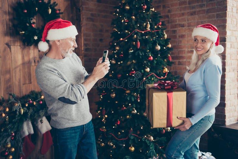 Un marito grigio-dai capelli di due genti che prende facendo foto sul gadg astuto fotografia stock