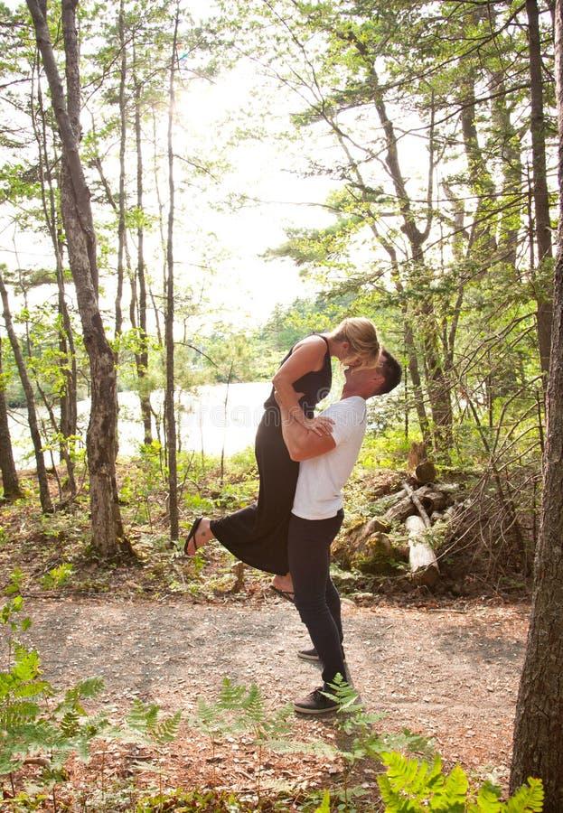 Un marito solleva la sua moglie in una posa romantica immagini stock