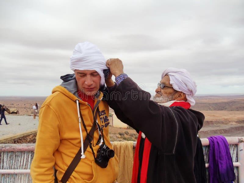 Un marocchino anziano sta facendo un turbante nazionale per il turista europeo fotografia stock libera da diritti