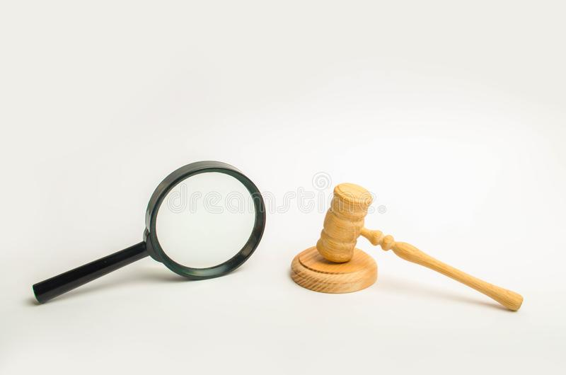 Un marteau du ` s de juge et une loupe sur un fond blanc Connaissance avec le cas, la recherche et l'évaluation juridiques de l'e images libres de droits