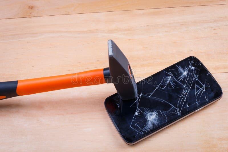 Un marteau lourd frappe l'écran d'un smartphone et le heurte Sur un fond en bois Plan rapproché photo libre de droits