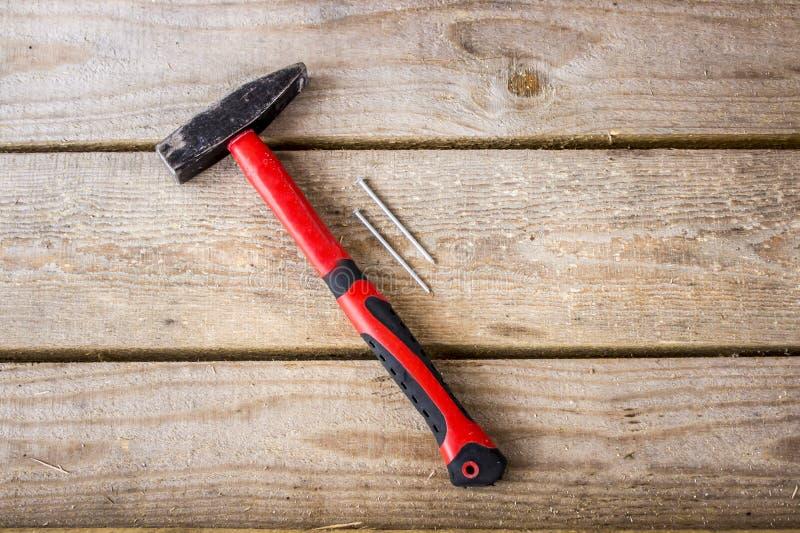 Un martillo con una manija roja y dos clavos imágenes de archivo libres de regalías