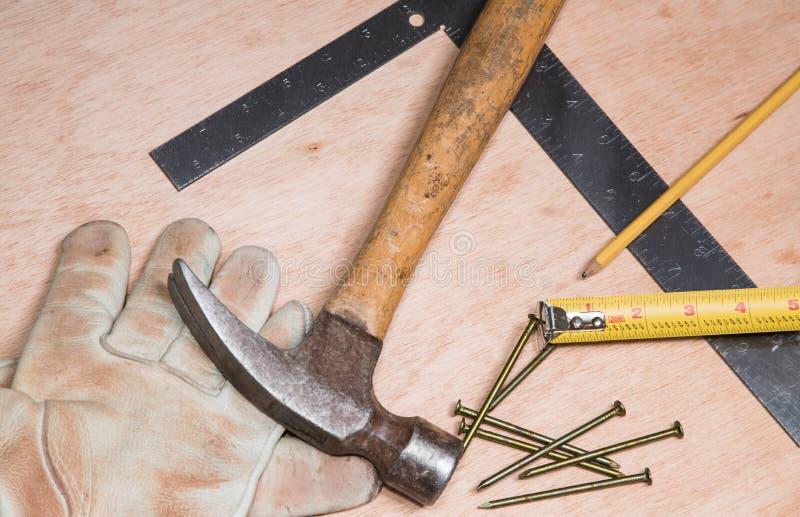 Un martillo, un cuadrado del metal, un lápiz, clavos y guantes viejos imágenes de archivo libres de regalías