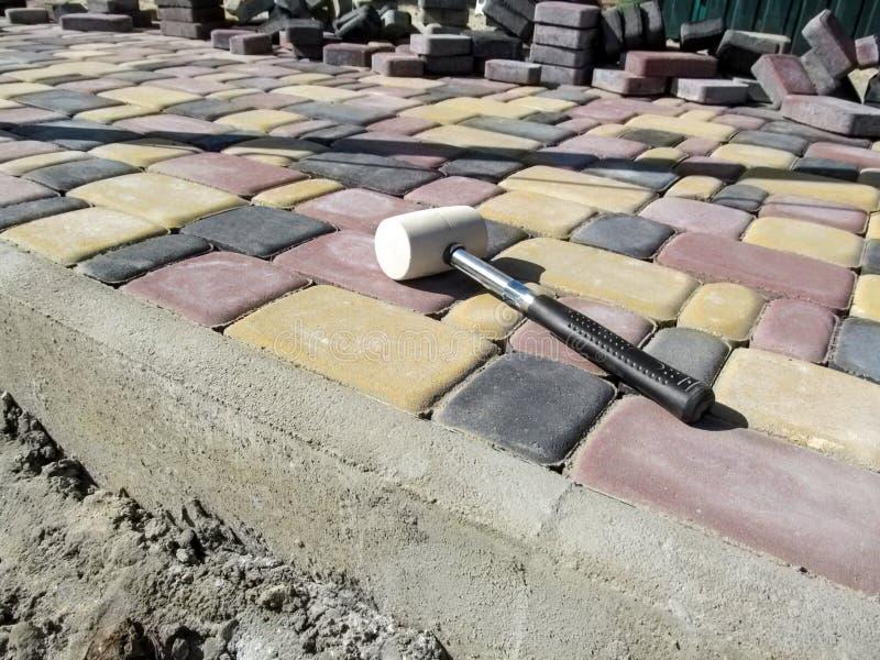 Un martillo de goma blanco miente en la superficie de una losa nuevamente puesta contra la perspectiva de pilas de tejas imagenes de archivo