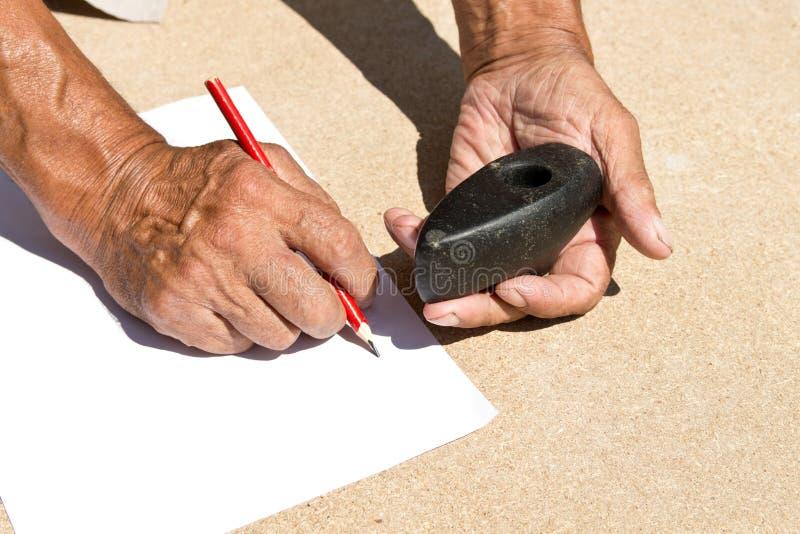 Un martillo de piedra viejo que un más viejo hombre se sostiene en sus manos archaeology Estudio de objetos antiguos foto de archivo