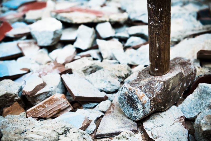 Un martillo usado para demoler el suelo de baldosas y la pared concretos de la casa antes de la renovaci?n ?l pesado y muy duro imagen de archivo