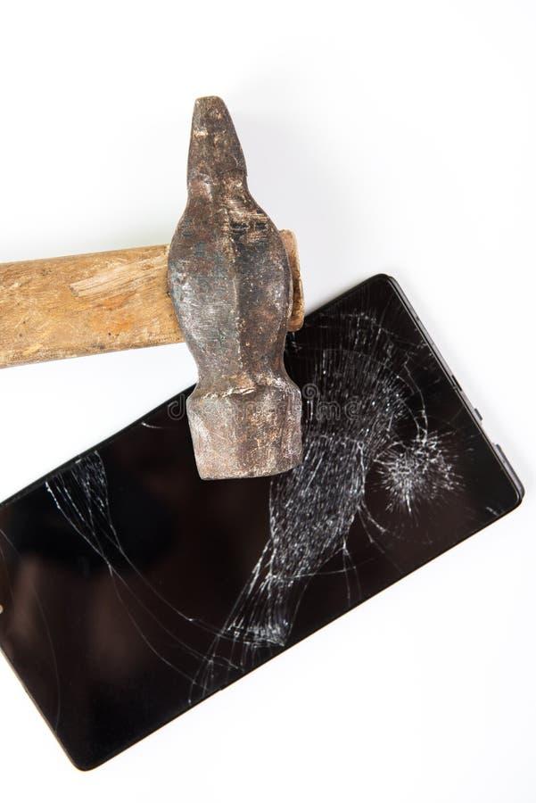 Un martillo y un smartphone viejos imagen de archivo libre de regalías