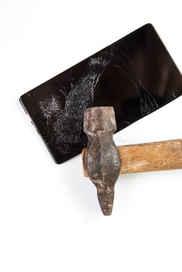 Un martillo y un smartphone viejos imágenes de archivo libres de regalías