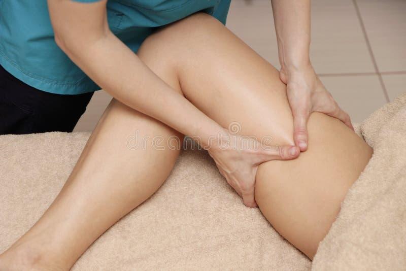 Un masajista que hace un masaje terapéutico del muslo para una mujer imagen de archivo