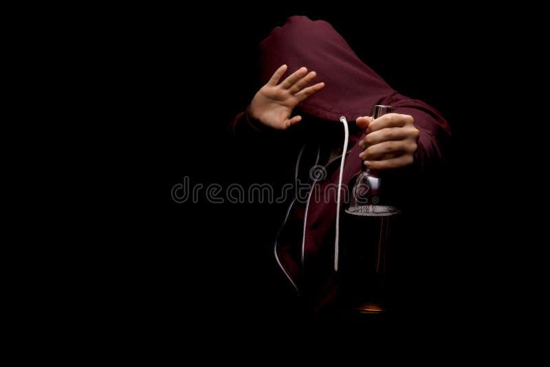 Un maschio adulto in un cappuccio rosso che tiene una bottiglia di birra in sua mano e che mostra un fanale di arresto su un fond fotografia stock