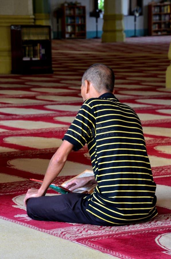 L'uomo musulmano legge Koran dentro la moschea immagine stock