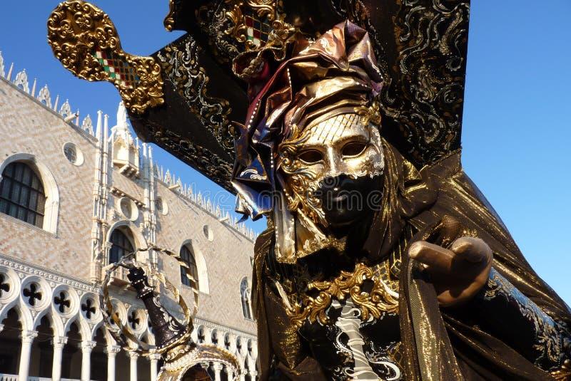 Un Masquerader dell'oro e del nero a Venezia fotografia stock