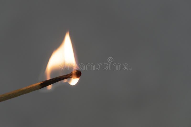 Un match allumé sur un fond gris Brûlures du feu image stock