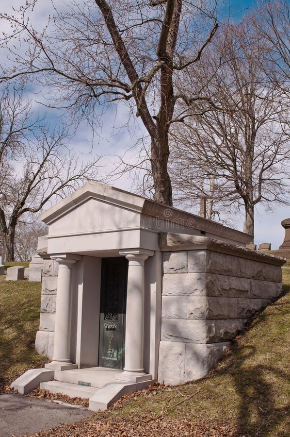 Un mausolée dans un cimetière avec les arbres nus d'hiver derrière lui images libres de droits