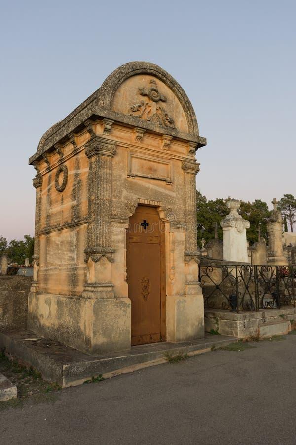 Un mausoleo con la cruz, la guirnalda y los pilares tallados en el Rosellón imagen de archivo