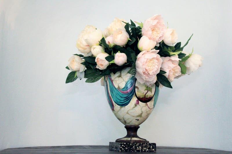 Un mazzo bianco del fiore della peonia in un vaso di colore su un fondo bianco fotografia stock