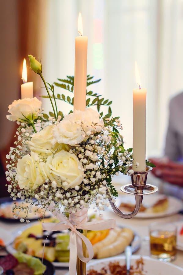 Un mazzo dei fiori e delle candele in un candeliere Regolazione festiva della tabella fotografie stock libere da diritti
