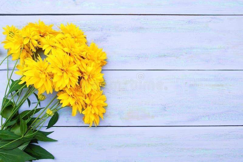 Un mazzo dei fiori gialli di Heliopsis su fondo di legno blu fotografia stock