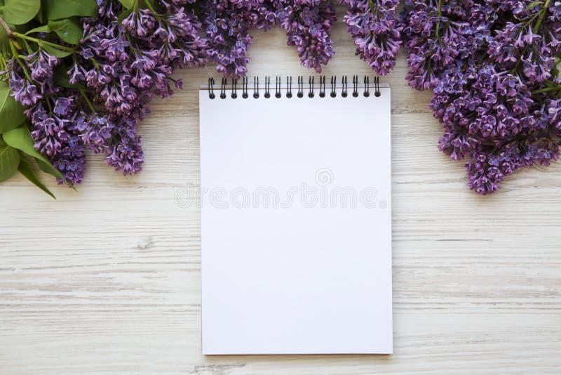 Un mazzo dei fiori lilla con il taccuino su un backg di legno bianco immagini stock libere da diritti
