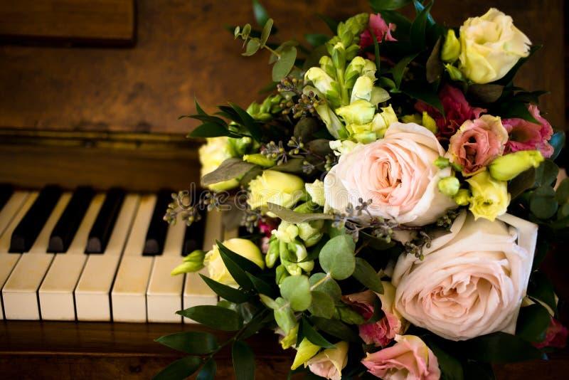 Un mazzo dei fiori sulle chiavi del piano immagini stock libere da diritti