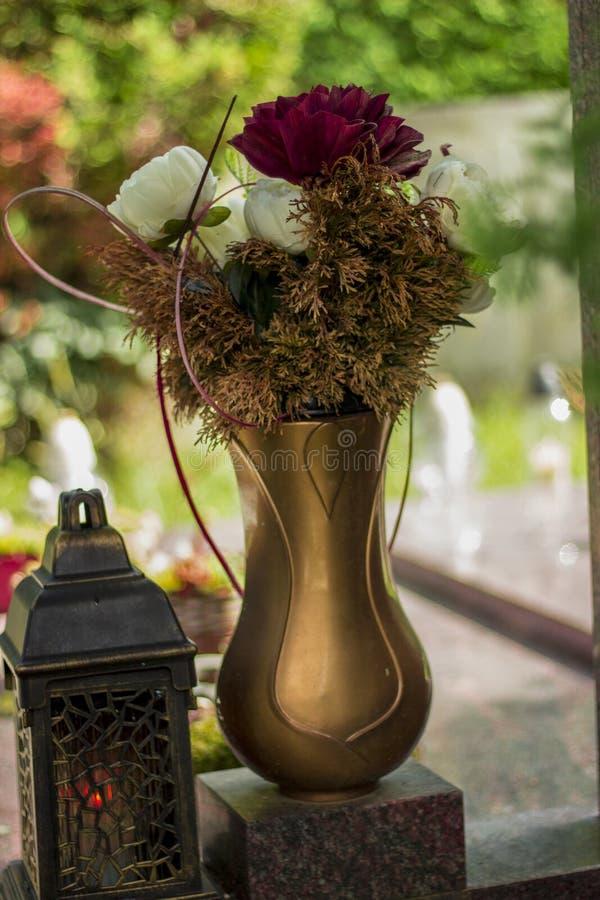Un mazzo dei fiori in un vaso dell'oro ed in una candela al cimitero per i giorni di tutti i san fotografie stock