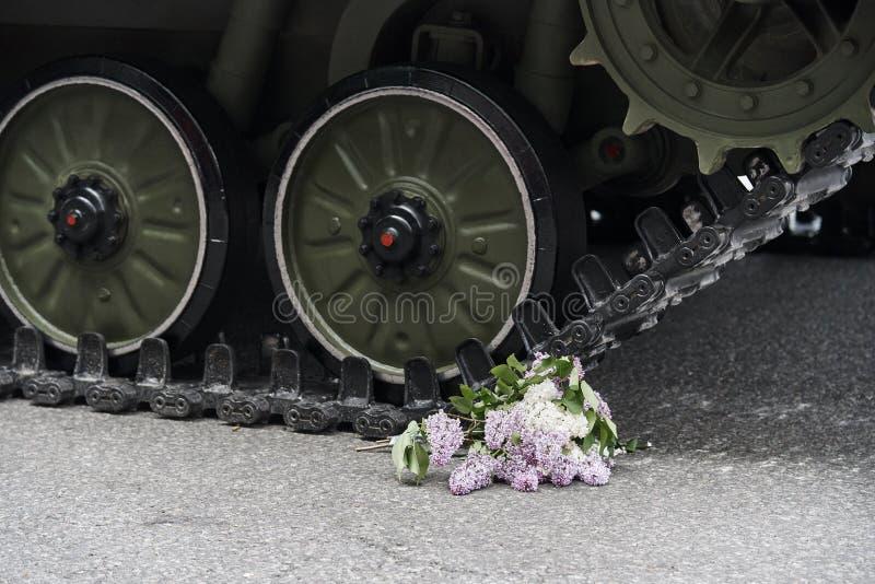 Un mazzo del lillà sotto le ruote del carro armato fotografia stock libera da diritti