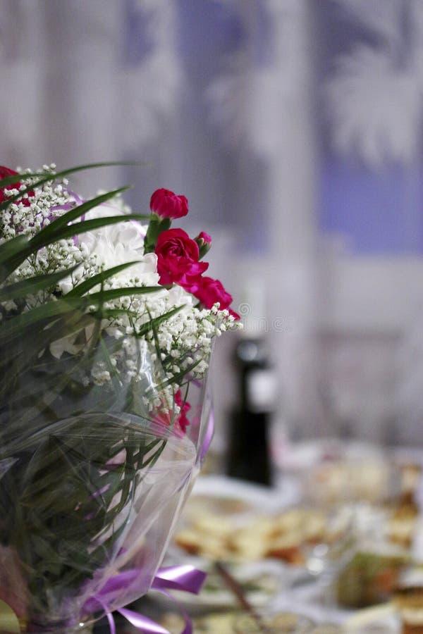 Un mazzo del primo piano differente dei fiori Una tavola festiva è veduta sui precedenti vaghi fotografia stock libera da diritti