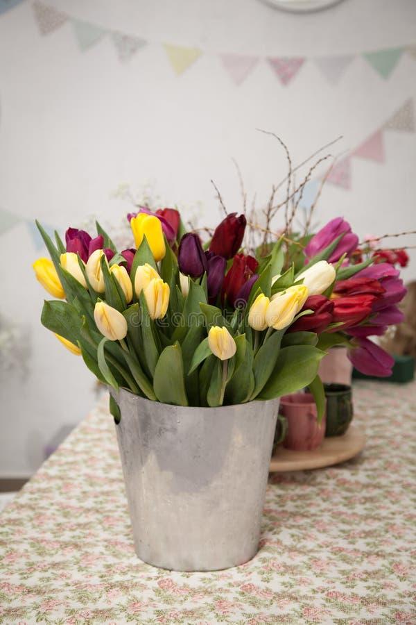 Un mazzo del tulipano fiorisce in un secchio del metallo fotografie stock