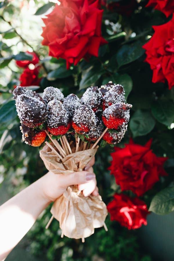 Un mazzo delle fragole coperte di cioccolato si chiude su delle rose rosse con differenti guarnizioni, dadi delle mandorle del ca immagine stock libera da diritti