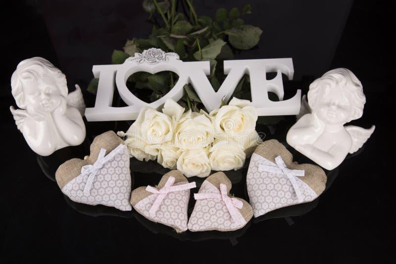 Un mazzo delle rose bianche, cuori ha fatto di materiale, angeli valentines fotografie stock