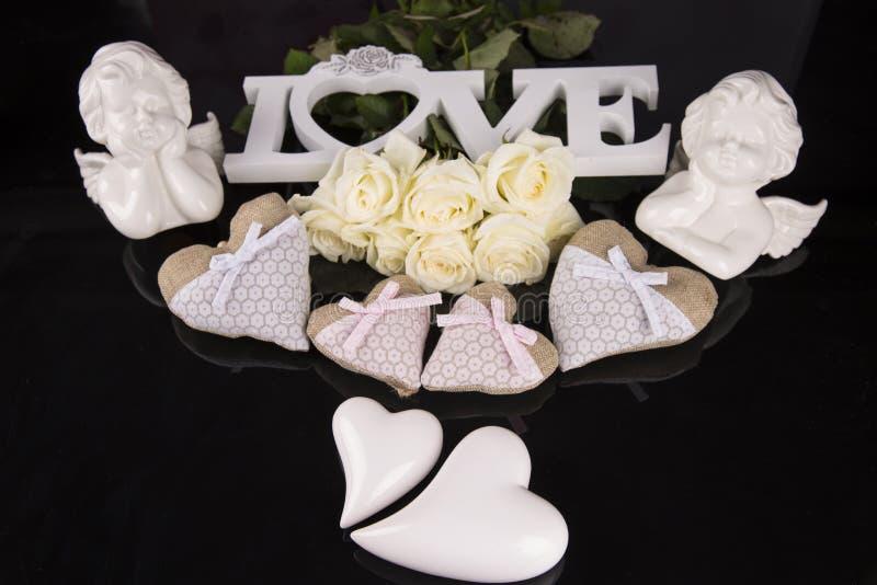 Un mazzo delle rose bianche, cuori ha fatto di materiale, angeli valentines immagini stock