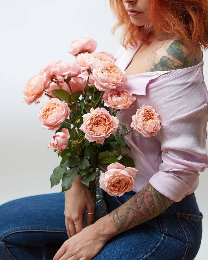 Un mazzo delle rose rosa in un vaso tiene una ragazza con un tatuaggio su un fondo grigio con lo spazio della copia St Giorno del fotografia stock libera da diritti