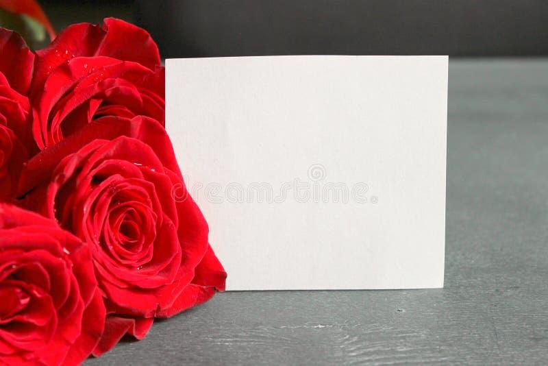 Un mazzo delle rose rosse e di uno strato di Libro Bianco per la scrittura, per scrivere il testo su un fondo nero di legno fotografie stock