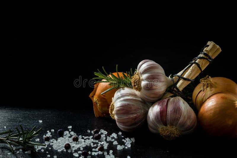 Un mazzo di aglio, di cipolla, di sale, di rosmarini e di bacche di ginepro fotografia stock