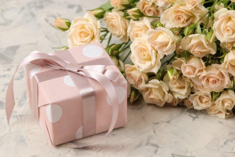 Un mazzo di belle mini rose tenere e di un contenitore di regalo su un fondo del cemento leggero feste presenti fotografia stock